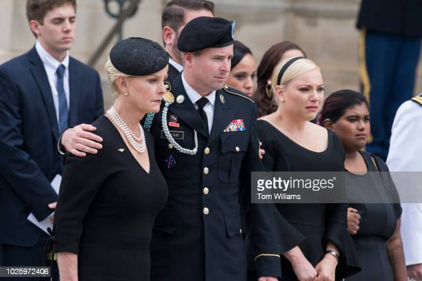 Cindy McCain the wife of the late Sen John McCain RAriz their son Jimmy daughters Meghan and Bridget right watch an Honor Guard carry his casket out...