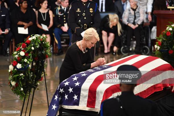Cindy McCain wife of John McCain prays at the casket of her husband as he lies in state at the US Capitol Rotunda in Washington DC on August 31 2018
