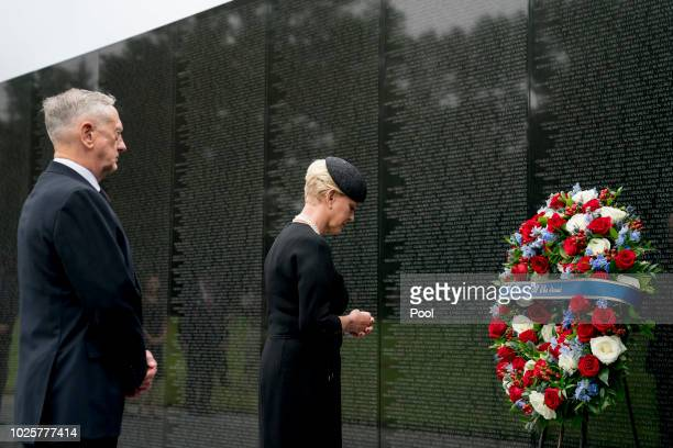 Cindy McCain, wife of, Sen. John McCain, R-Ariz., accompanied by Defense Secretary Jim Mattis, left, lays a wreath at the Vietnam Veterans Memorial...