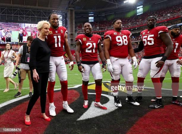 Cindy McCain, wife of the late U.S. Sen. John McCain, R-Ariz., embraces Arizona Cardinals' Larry Fitzgerald, Patrick Peterson, Corey Peters and...