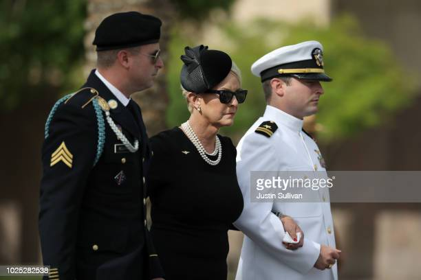 Cindy McCain wife of US Sen John McCain is escorted by her sons Jack and Jimmy as her husband's casket is removed from the Arizona State Capitol to...