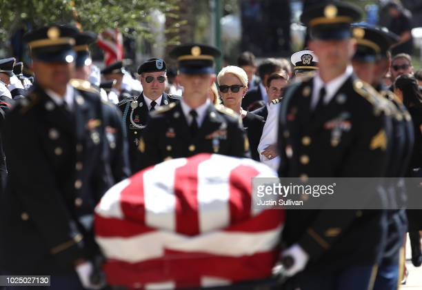 Cindy McCain wife of US Sen John McCain walks behind his casket as it is carried into the Arizona State Capitol on August 29 2018 in Phoenix Arizona...
