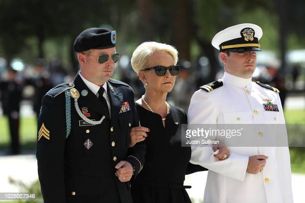 Cindy McCain wife of US Sen John McCain walks into the Arizona State Capitol with sons James McCain and Jack McCain on August 29 2018 in Phoenix...