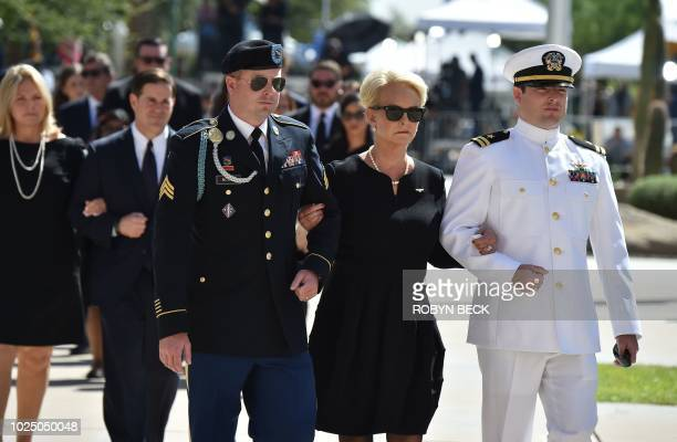 Cindy McCain wife of US Senator John McCain walks into the Arizona State Capitol Rotunda escorted by sons James McCain and Jack McCain August 29 2018...