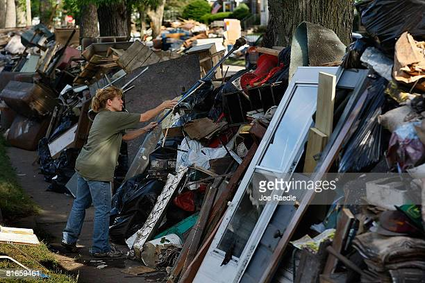 Cindy Pansegrau throws garbage on top of a block's long pile of household goods that were ruined by the flood water of the Iowa River June 21, 2008...