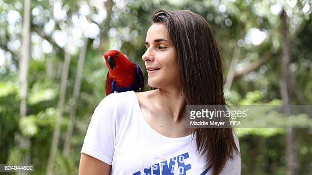 Cindy Perrault of France looks at a Eclectus parrot perched on her shoulder at the Port Moresby Nature Park on November 18, 2016 in Port Moresby,...