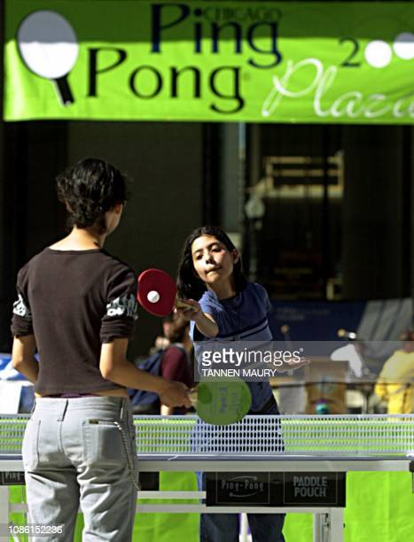 Cindy Rosillo hits her return to playing partner RoseAnn Rosillo while playing pingpong in Chicago's Daley Plaza 04 August 2000 The city is setting...