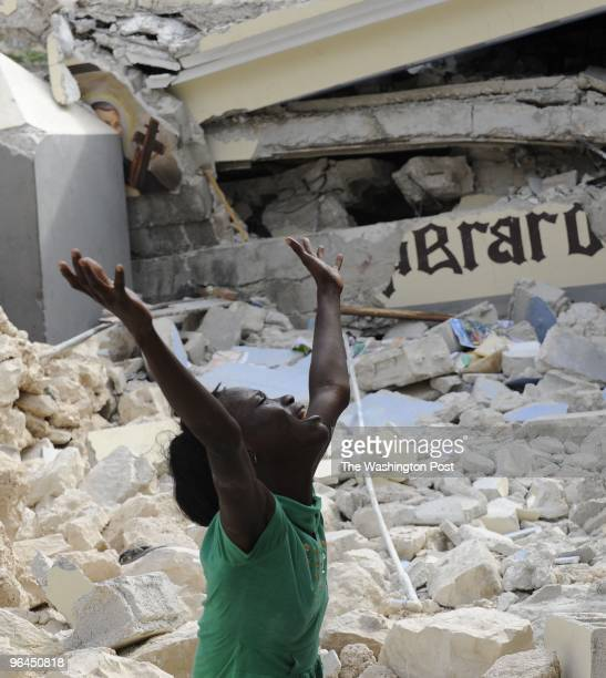Cindy Tersme weeps for her brother Jean Gaelle Dersmorne 14 years old amid the rubble of the earthquake as he crawls past a schoolgirl that died at...