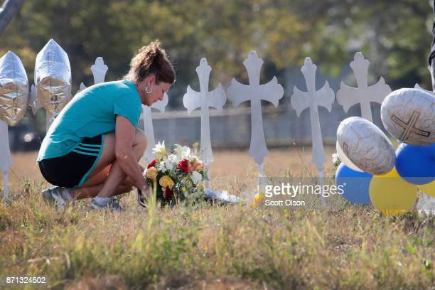 Cindy Wyatt of Sutherland Springs lays flowers at a memorial where 26 crosses stand in a field on the edge of town to honor the 26 victims killed at...
