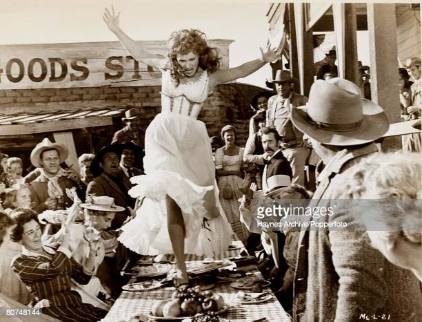 Cinema American film actress Maureen O'Hara dances on the table in a still from the film Man Of Truth aka 'McLintock' 1963