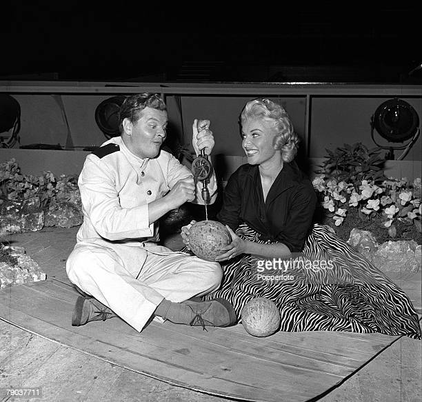 Cinema London England British actor comedian and entertainer Benny Hill is pictured with actress Belinda Lee as he drills a hole in a watermelon on...