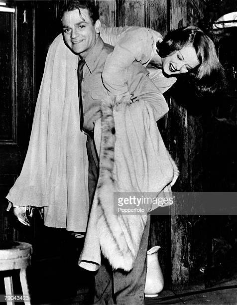 circa 1930's American film actress Bette Davis is pictured in a lighthearted picture as she is picked up and carried by fellow American actor James...