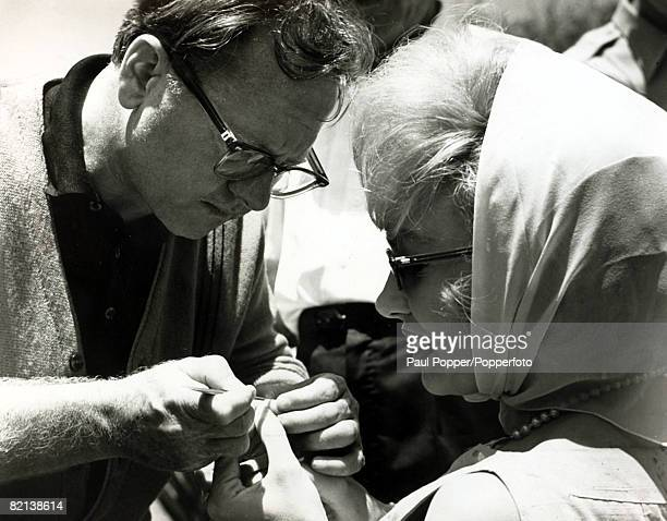 October 1963 American actress Edie Adams born 1927 has a splinter removed from her finger by fellow actor Mickey Rooney on the set of the film 'It's...