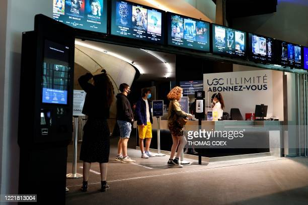 Cinemagoers buy tickets prior to a movie screening in a film theatre on June 22 2020 in Paris following the reopening of French theatres as France...