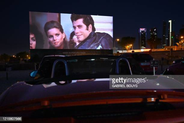 TOPSHOT Cinemagoers in their cars attend the screening of the US musical romantic comedy film Grease during the reopening of the Autocine Madrid Race...