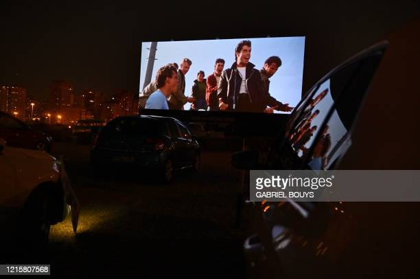 Cinemagoers in their cars attend the screening of the US musical romantic comedy film Grease during the reopening of the Autocine Madrid Race drivein...
