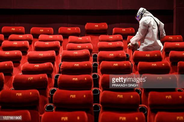 Cinemas employee wearing a Personal Protective Equipment suit sanitises a cinema hall as part of preparations for a possible reopening amid concerns...