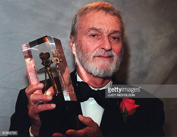 US cinematographer Conrad Hall poses with the ASC Outstanding Achievement Award for his film American Beauty in Los Angeles 20 February 2000 Hall has...