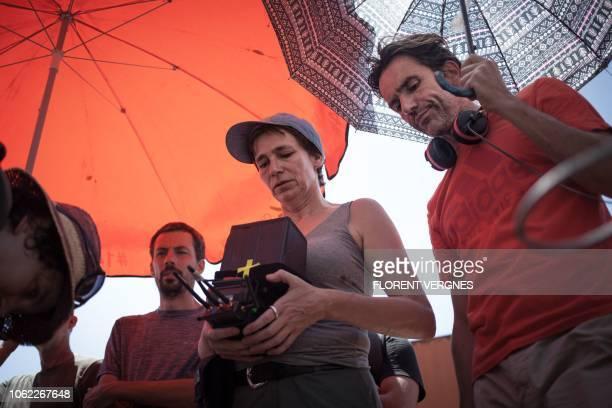 Cinematographer Elin Kirschfink and film director Boris Lojkine watch the latest scene shot in the street of Bangui on October 21 2018 for the film...