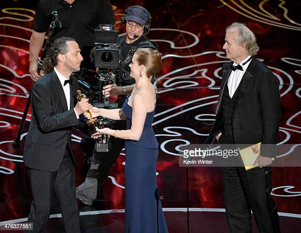 Cinematographer Emmanuel Lubezki accepts the Best Achievement in Cinematography award for 'Gravity' from actors Amy Adams and Bill Murray onstage...