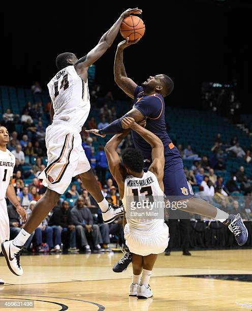 Cinmeon Bowers of the Auburn Tigers is called for a charge as Daniel Gomis and Langston MorrisWalker of the Oregon State Beavers defend during the...