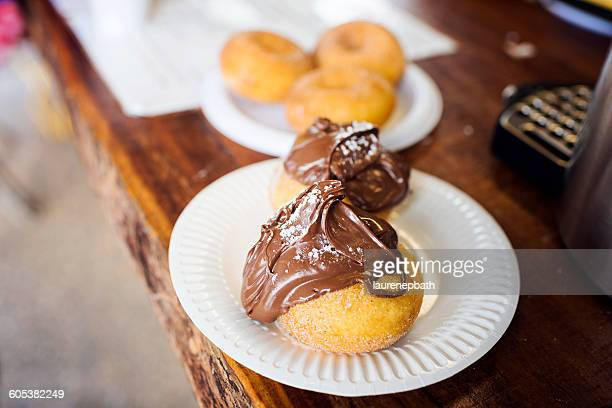 Cinnamon donuts covered in chocolate spread on a plate