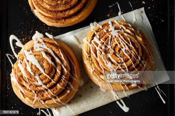 Cinnamon Rolls drizzled with icing on wax paper