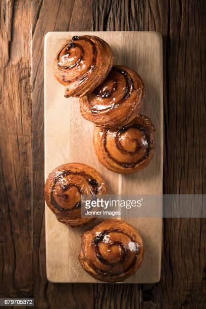 Cinnamon Rolls On Chopping Board.