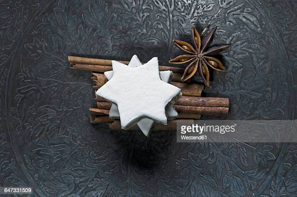 Cinnamon stars, cinnamon sticks and star anise on metal plate