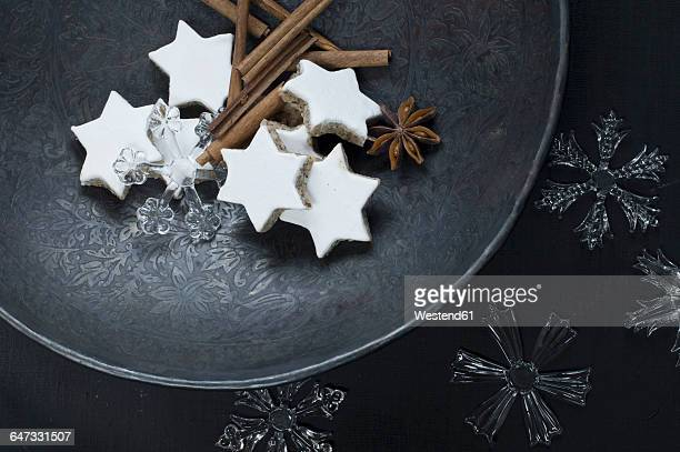 Cinnamon stars, cinnamon sticks, star anise and decoration on metal plate