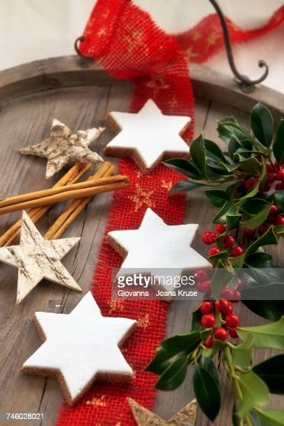 Cinnamon stars, sprigs of holly, cinnamon stick and wooden stars