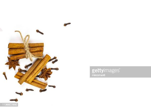 cinnamon sticks on ground cinnamon. mixed spices - gewürznelke stock-fotos und bilder