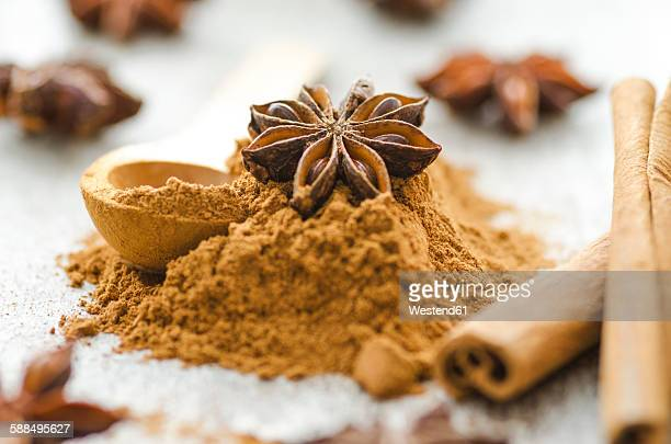 Cinnamon sticks with ground cinnamon and anise stars on a wooden table