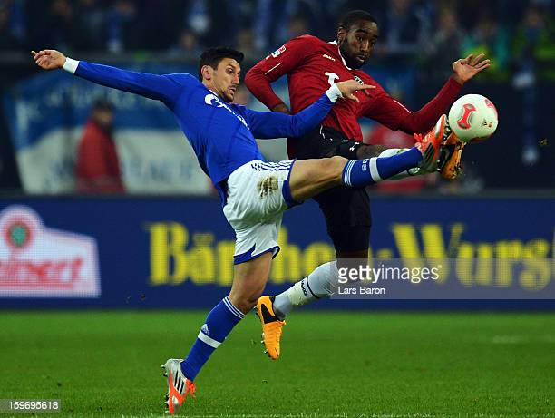 Ciprian Marica of Schalke is challenged by Johan Djourou of Hannover during the Bundesliga match between FC Schalke 04 and Hannover 96 at...