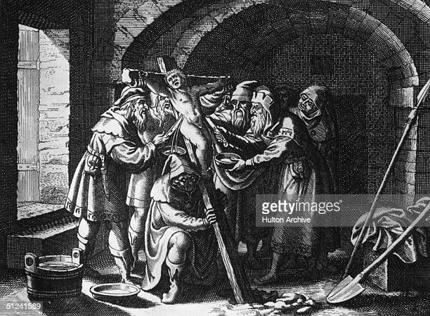 Circa 1478 A group of men with daggers pierce the sides of a child who is nailed to a cross and collect the blood pouring out Antisemitic propaganda...
