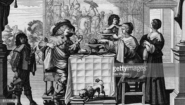 Circa 1650 A group of people wearing clothes in the early Baroque or Cavalier style sit down to a small banquet together in front of a rich tapestry