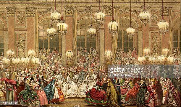 Circa 1750 An 18th century masquerade held in a magnificent ballroom brightly lit with chandeliers and candelabra Some people are in fancy dress...