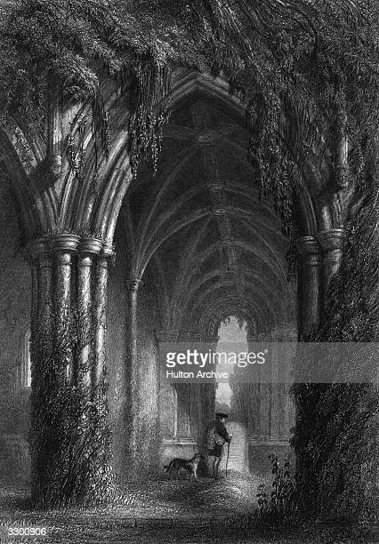 Man and dog walking through the cloisters at Dryburgh Abbey in Scotland. The Abbey was founded around 1150 and the first abbot, recorded only as...