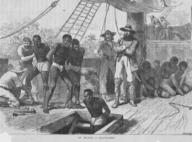 Slaves aboard a slave ship being shackled before being...
