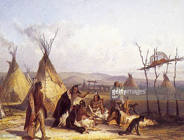 Mourners sitting by the burial platform of a Sioux chief erected in the centre of their encampment