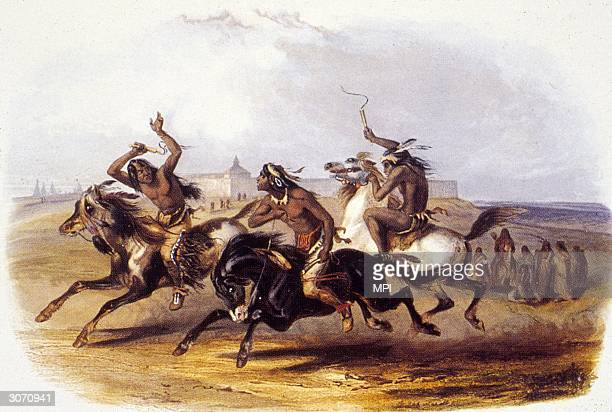 Three Sioux Indians compete in a horse race, lashing their mounts into a frenzy with whips.