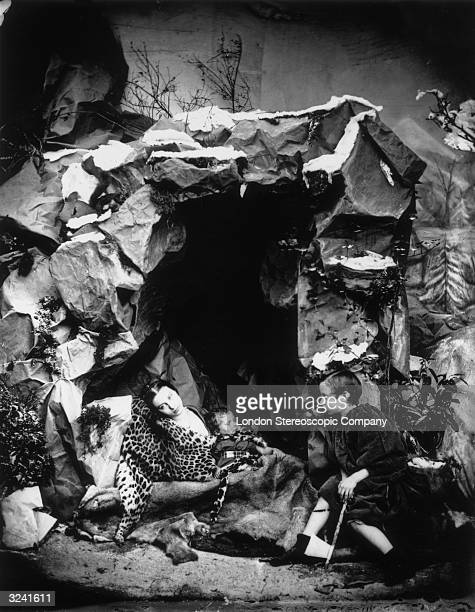 A woman lies at the mouth of a cave wrapped in a leopard skin and accompanied by two small boys London Stereoscopic Company Comic Series 144