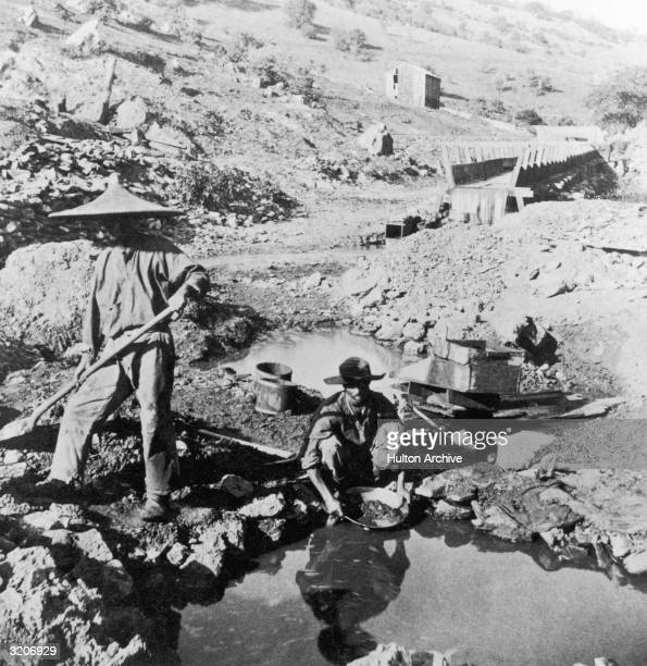 Chinese workers panning for gold in California. A man in a coolie hat digs as another man kneels and sifts.