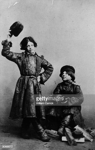 A couple of young Russian boys one striking a dancing pose while the other claps his hands