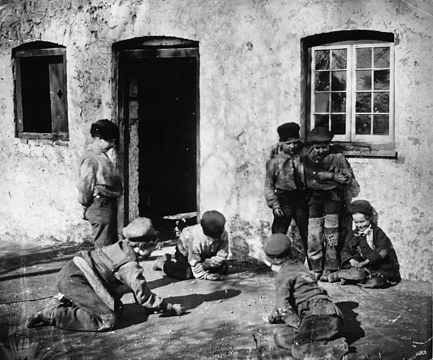 A group of boys in ragged clothing play a game of marbles...