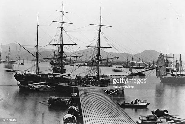 A sailing ship docked at a jetty in Hong Kong harbour surrounded by other boats