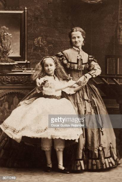 A young girl and an older woman in Victorian knickerbockers and full skirts