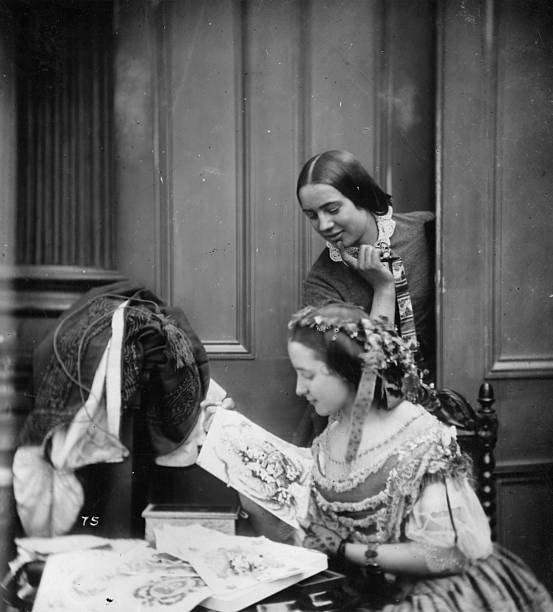 Two victorian women admiring Valentine cards, in a...