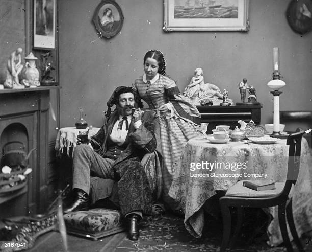 A pampered victorian husband relaxes in his dressing gown and hat while his wife lights his pipe with a taper London Stereoscopic Company Comic Series