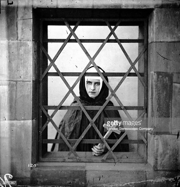 A young nun holding a cross whilst looking through a barred window London Stereoscopic Company Comic Series 126